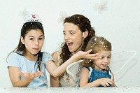 Girl throwing confetti, mother and sister watching