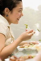 Side profile of a female office worker having lunch and smiling