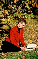 Woman in park, reading a book