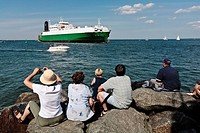 Tourists sitting on rocks at coast looking at container ship, Warnemunde, Mecklenburg_Vorpommern, Berlin, Germany