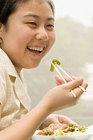 Close_up of a female office worker having lunch with chopsticks and smiling