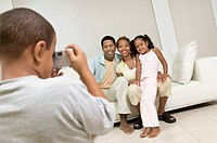 Boy Taking Picture of Family on sofa in living room
