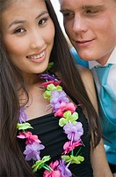 Well_dressed teenage couple wearing leis outside school dance