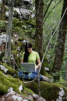young woman with laptop in the wood