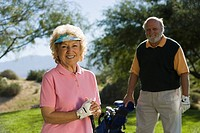 Senior couple in golf course smiling focus on woman portrait