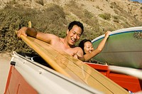 Surfer couple taking surfboards from back of truck
