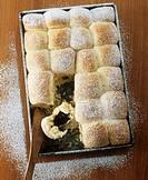 Buchteln yeast dumplings with powidl stewed plums on baking tray