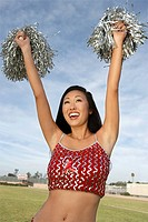 Cheerleader with pom poms raised
