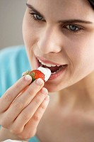 Young woman eating a strawberry dipped in yoghurt
