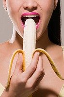 Close_up of a young woman eating a banana