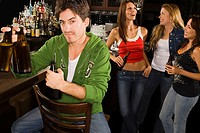 Portrait of a young man holding beer bottles at a bar counter with his three friends standing behind him
