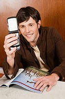 Young man holding a mobile phone in a cafe and smiling