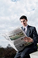Portrait of a businessman sitting at the edge of a wall and reading a newspaper