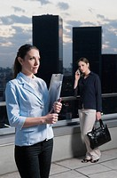 Businesswoman holding a file and another businesswoman talking on a mobile phone behind her