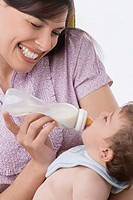 Close_up of a mid adult woman feeding her son with a baby bottle