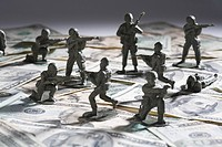 Close_up of plastic toys fighting on paper currency