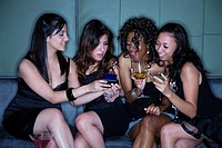 Women in nightclub drinking cocktails and text messaging on cell phone