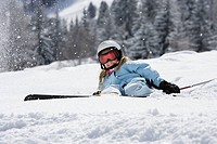 Girl with skis lying on snow