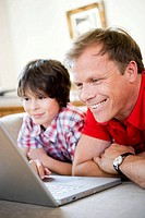 Father and son smiling into laptop
