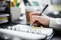 Businesswoman Writing in Weekly Organizer