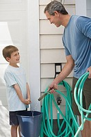 Father and young son filling bucket with hose