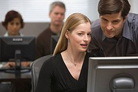 Businessman and businesswoman looking at computer