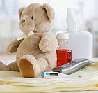 Teddy bear, medication, thermometer and telephone on blanket