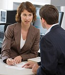 Businesswoman and businessman discussing paperwork