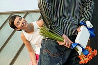 Young couple, man hiding present and flowers behind back