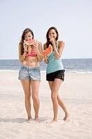 Women eating watermelon at beach