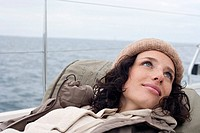 Germany, Baltic Sea, Lübecker Bucht, Portrait of a young woman lying on deck of yacht, smiling