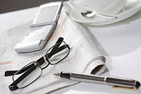 Cup of coffee with saucer, pen and spectacles on newspaper, close_up
