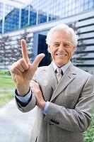 Germany, Baden Württemberg, Stuttgart, Senior businessman holding up two fingers, smiling, portrait