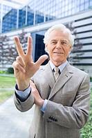 Germany, Baden Württemberg, Stuttgart, Senior businessman holding up three fingers, smiling, portrait