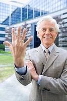 Germany, Baden Württemberg, Stuttgart, Senior businessman showing hand, smiling, portrait