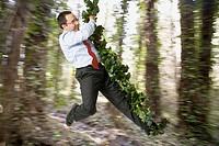 Hispanic businessman swinging on forest vine