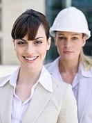Germany, Baden_Württemberg, Stuttgart, Two businesswomen, one with hard at, portrait