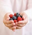 Child holding handful of berries