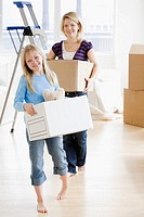Mother and daughter carrying moving boxes