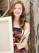 Young woman holding paintbrushes and canvas