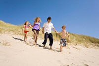 Germany, Baltic sea, Family running down sand dunes