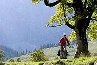 Austria, Tyrol, Ahornboden, Woman mountain biking