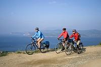 Italy, Tuscany, Elba, Mountainbikers riding across coastline