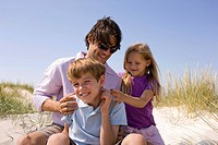 Germany, Baltic sea, Father and children on sand dunes, portrait