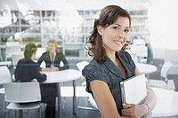 Businesswoman holding laptop in office