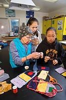 Elder native Yupik woman teaches youth to do bead work @ Akiak High School inside Western Alaska
