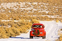 Santa driving a vintage red Ford pick_up truck down a snowcovered rural road in the Rio Grande Valley of New Mexico