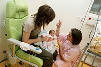 ENTERAL FEEDING Photo essay at the hospital of Meaux 77, France. Department of neonatology. The pediatric nurse is holding in her arms a premature chi...
