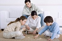 Family spending time together, mother and children playing dominoes, father watching