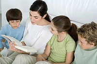 Woman reading story to her children